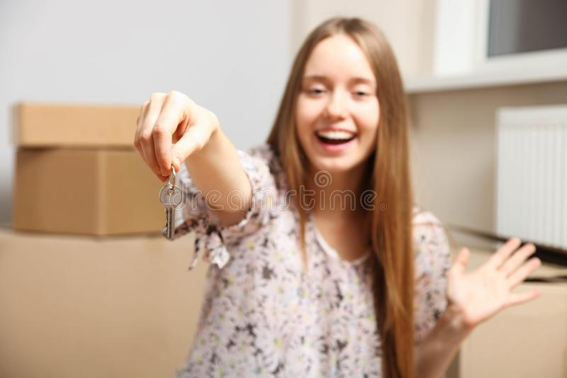 Girl with keys sits on background of cardboard boxes in new apartment stock photo