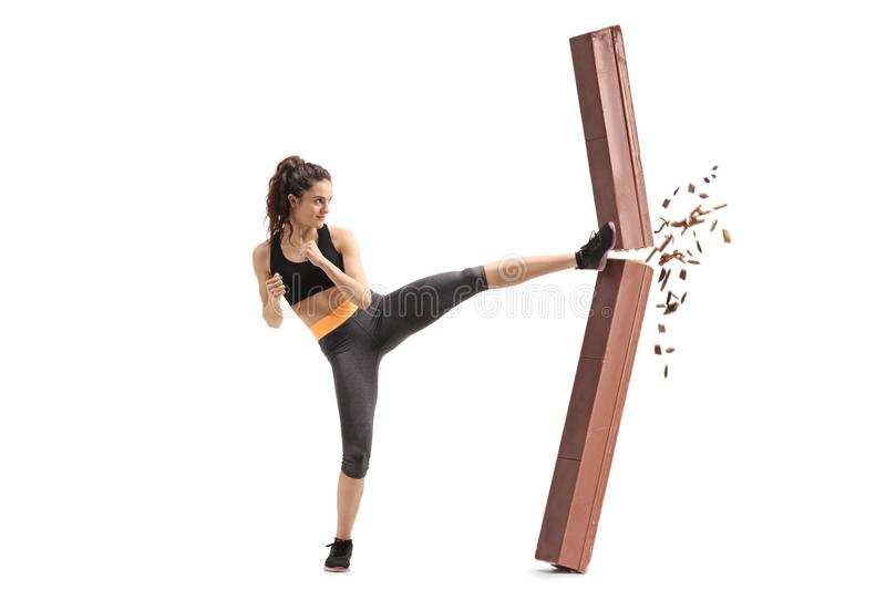 Girl kicking and breaking a chocolate bar royalty free stock image
