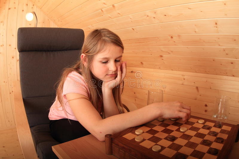 Girl - kid concentrating on draughts. Concentrated girl sitting on armchair - blond Caucasian kid playing draughts or checkers on chessboard in wooden attic room royalty free stock images