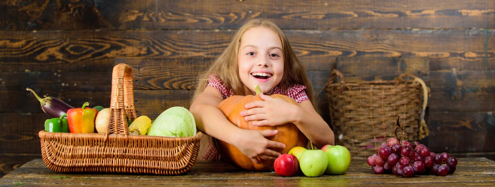Girl kid at farm market with organic vegetables. Grow your own organic food. Kid farmer with harvest wooden background. Harvest festival concept. Child little royalty free stock image