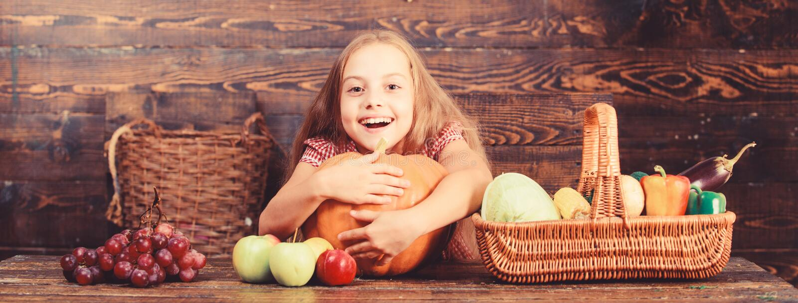 Girl kid at farm market with organic vegetables. Grow your own organic food. Kid farmer with harvest wooden background. Harvest festival concept. Child little royalty free stock photo