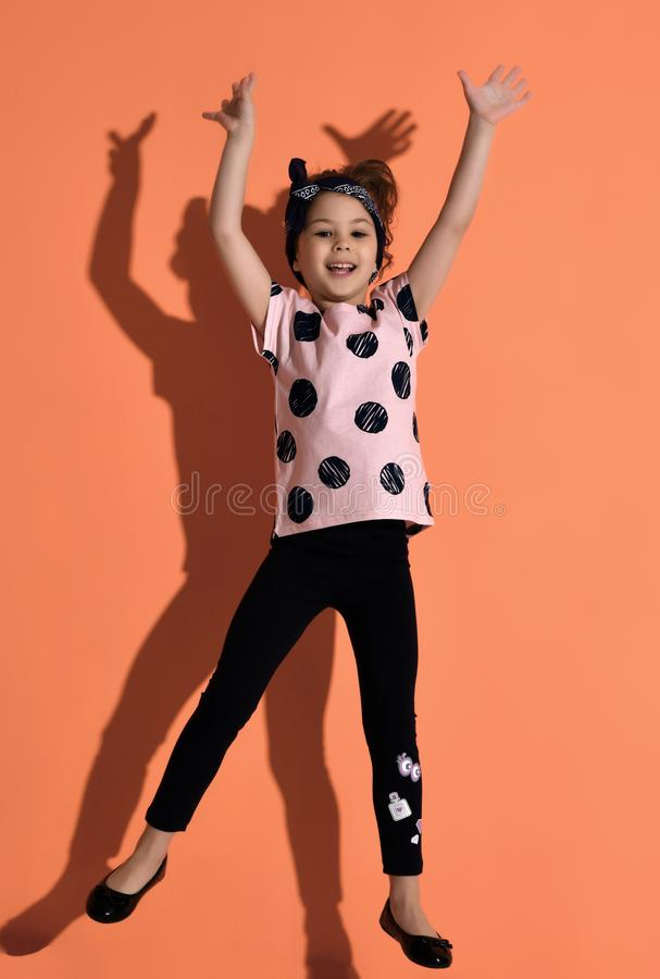 Girl kid jumping in  pink summer shirt  with hands up on orange background stock photo