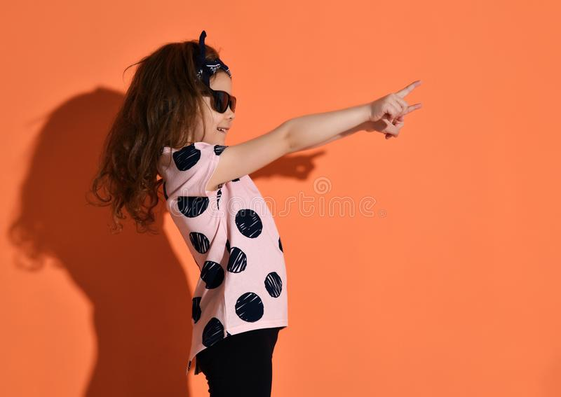 Girl kid posing in summer shirt and sunglasses pointing fingers up on orange background royalty free stock image