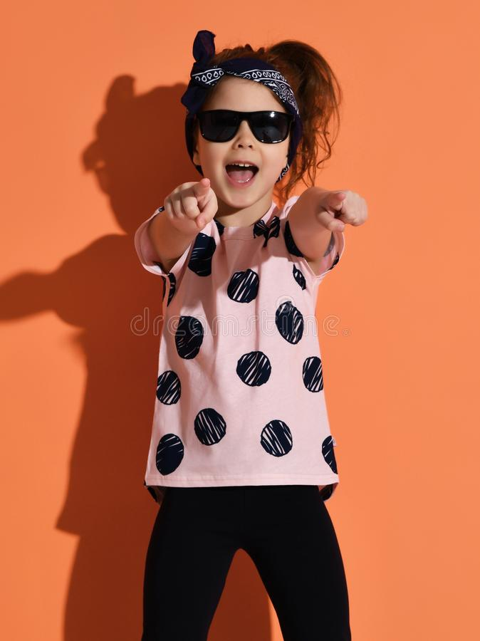 Girl kid posing in summer shirt and sunglasses pointing fingers up on orange background stock images
