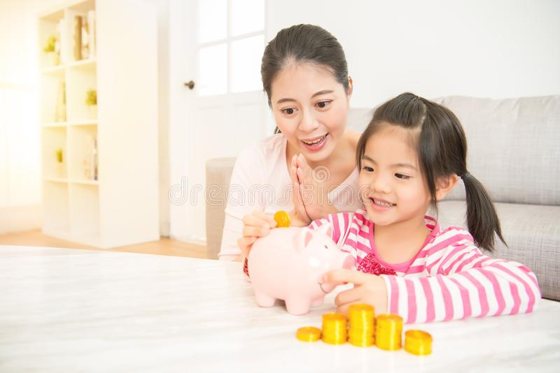 Girl kid putting money into piggy bank stock photos