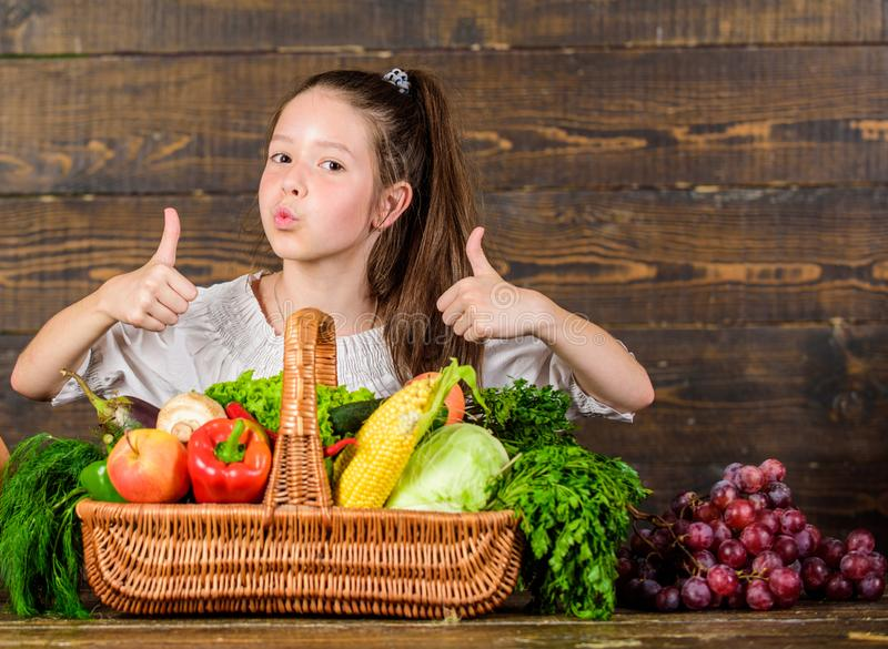 Girl kid rustic style farmers market with fall harvest. Child show thumbs up celebrate harvest holiday vegetables basket. Kid farmer with harvest wooden stock photography
