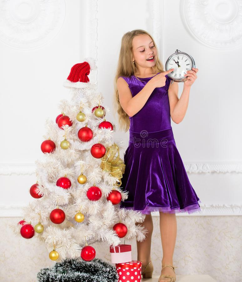Girl kid santa hat costume with clock counting time to new year. How much time left. Last minute till midnight. New year royalty free stock photography