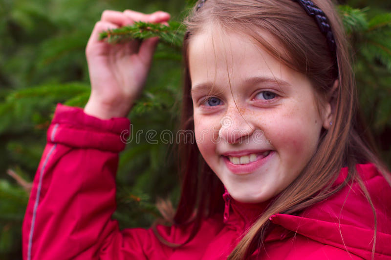 Girl kid smiling and posing near the green tree royalty free stock image