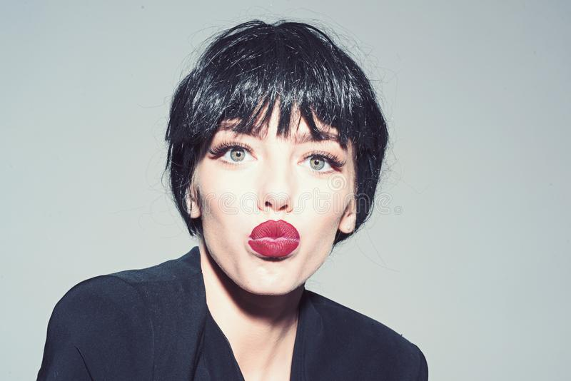 Girl on kissing face wears black formal jacket. Lady in black wig with make up on grey background. Woman with attractive. Red lips looks at camera. Kiss and stock images