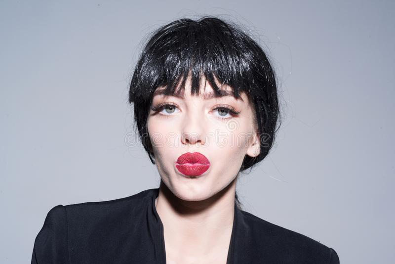 Girl on kissing face wears black formal jacket. Lady in black wig with make up on grey background. Kiss and lipstick. Concept. Woman with attractive red lips royalty free stock photos