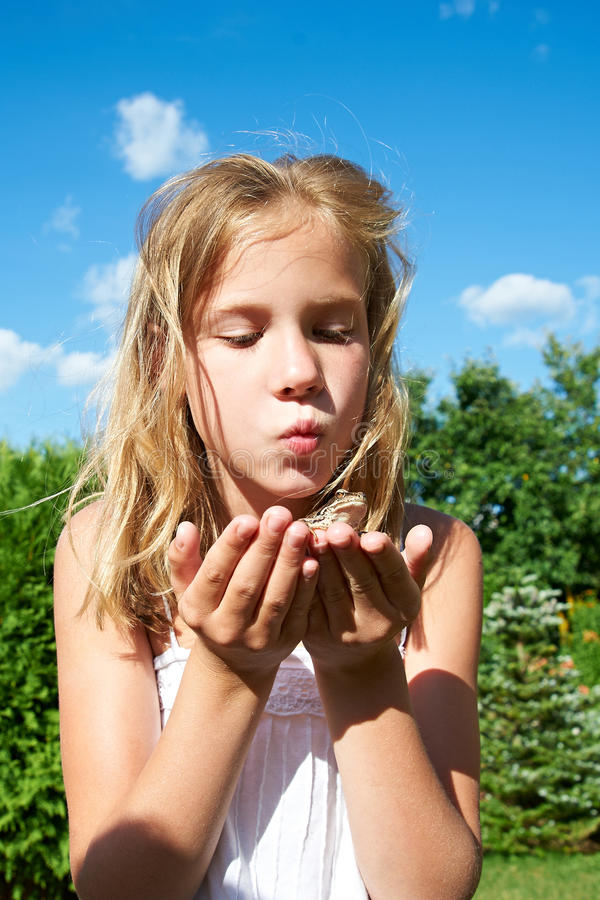 Girl kissing a frog royalty free stock image
