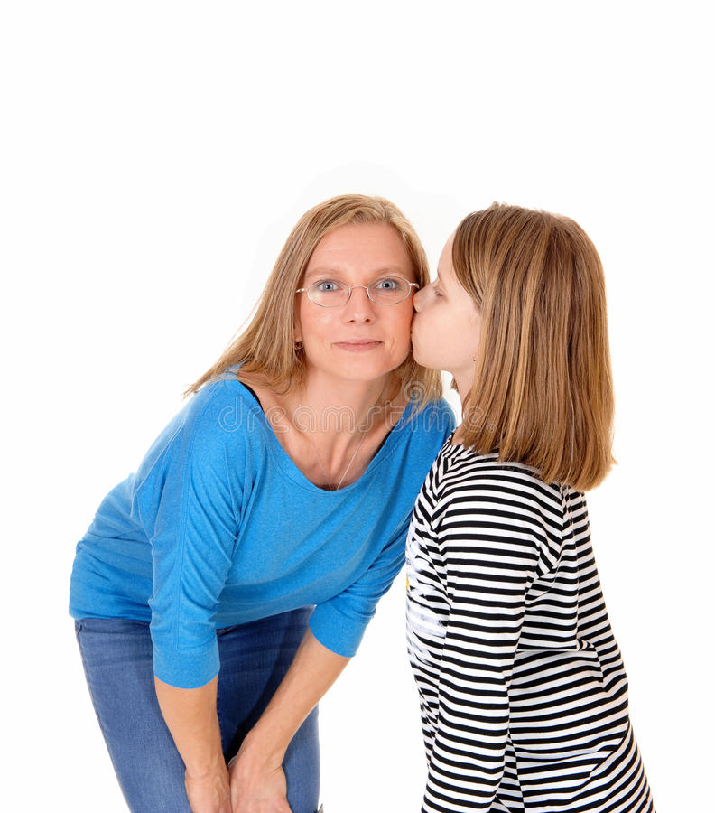 Girl kissing her mom. A young pretty girl kissing her mom on the chick, isolated for white background royalty free stock image