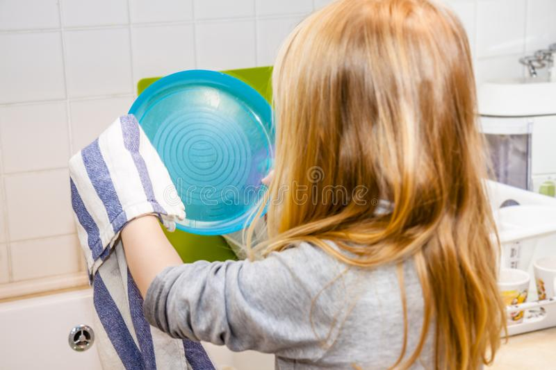 Girl in the kitchen with a plate and towel in his hand at the sink royalty free stock image