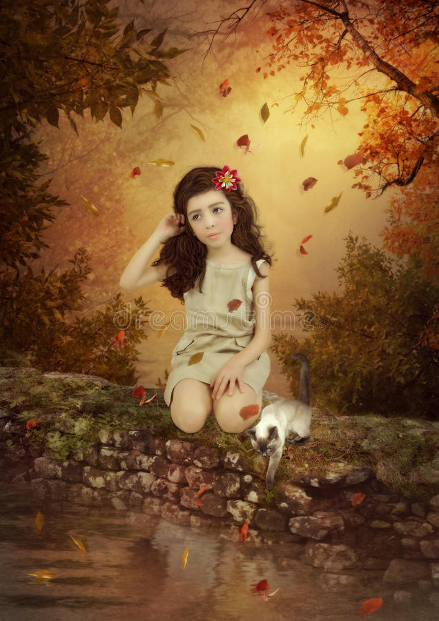 Girl and kitten. Little girl with long hair and kitten sitting on the stone above the water on the background of the autumn landscape surrounded by colorful