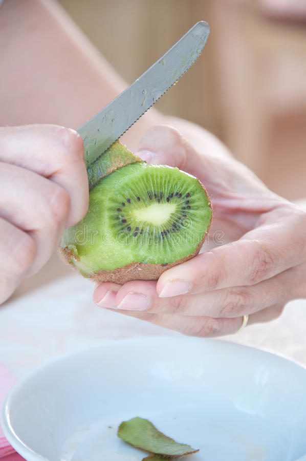 Girl with a knife peeling a kiwi fruit royalty free stock photography