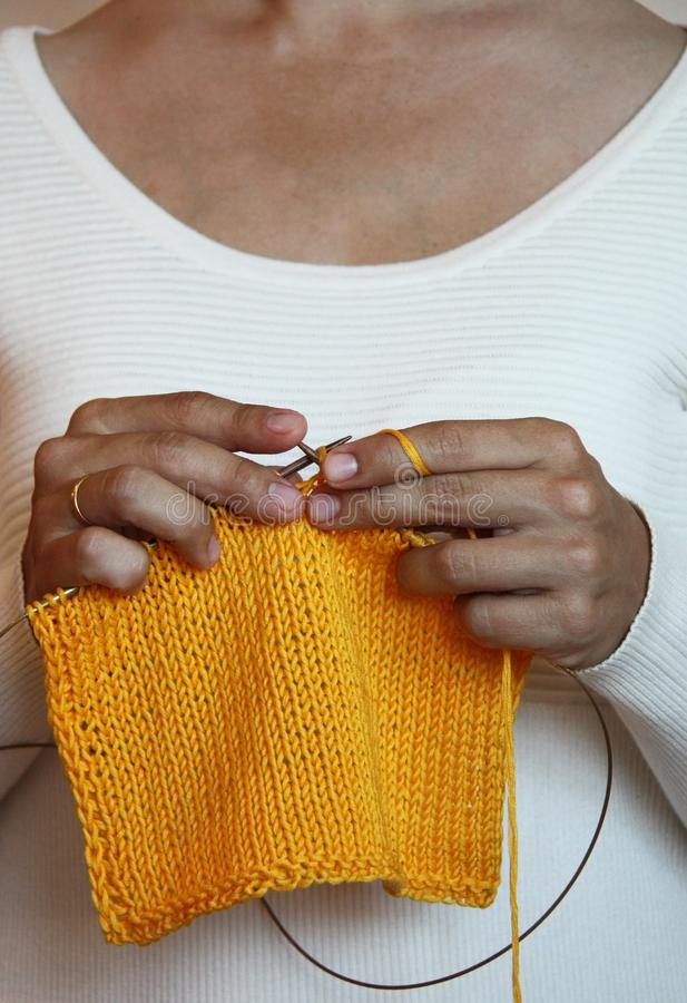 A girl knits cotton clothes. Close-up knitting on knitting needles. royalty free stock photography