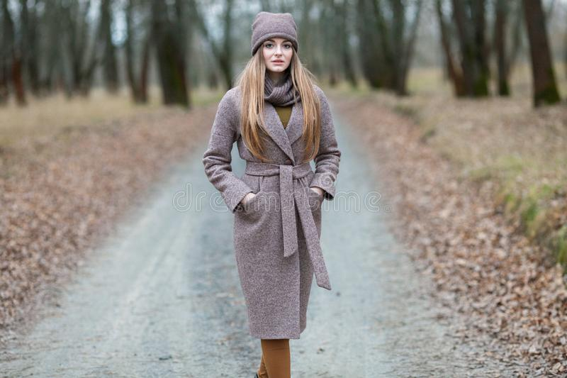 Girl in a knitted cap and scarf on a road in the autumn in the nature. stock photos
