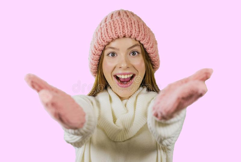 Girl in knitted hat and gloves is smiling and holding out her hands in greeting on an isolated background royalty free stock photo