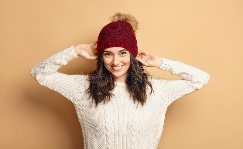 Girl in Knitted Sweater and Beanie Hat over beige background. Funny Hipster Girl in Knitted Sweater and Beanie Hat over beige soft Background. Trendy Casual stock photos