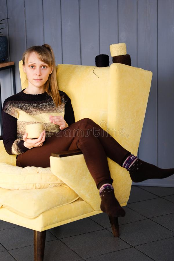 A girl in a knitted sweater holding a coil of colored yarn in his hands, sitting in a yellow chair. A young woman draw a thread stock images