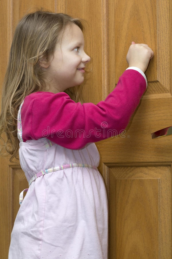 Knocking. A vertical picture of a happy and smiling young blond haired girl knocking on a door royalty free stock photography