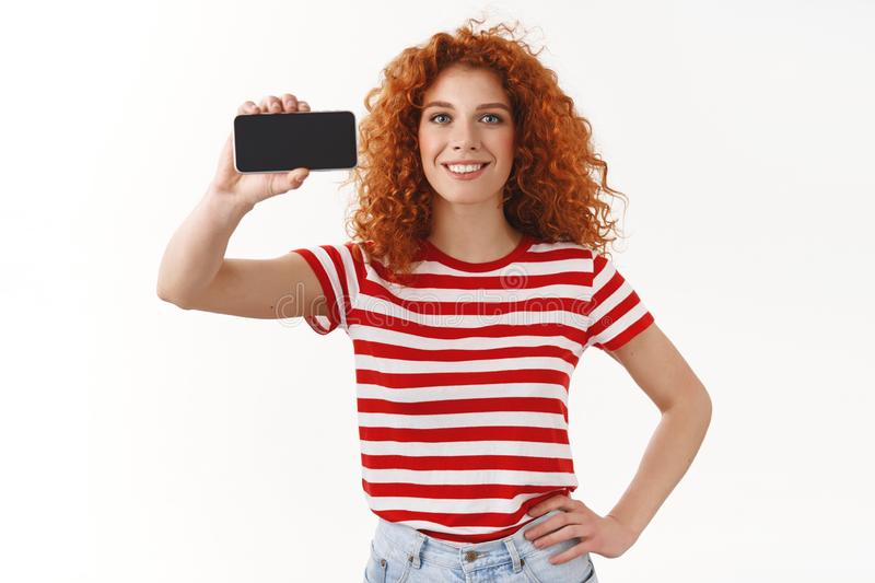 Girl knows last digital trends. Attractive charismatic ginger girl curly hairstyle blue eyes hold hand waist showing royalty free stock photos