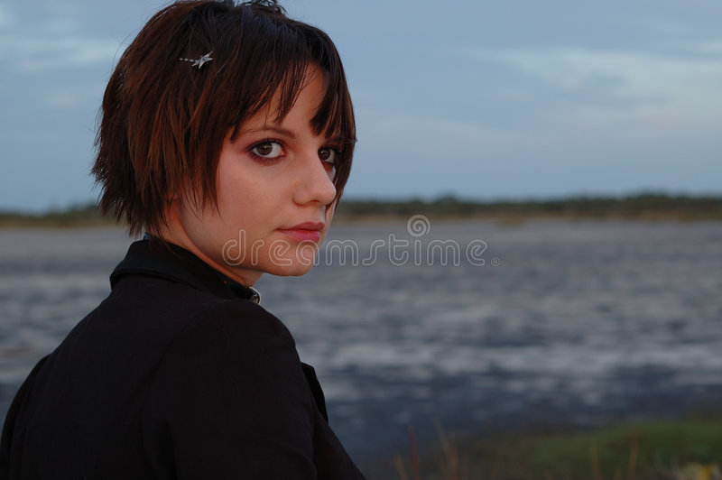 Girl By Lake. Young woman looking off into the distance while walking past a lake stock photos