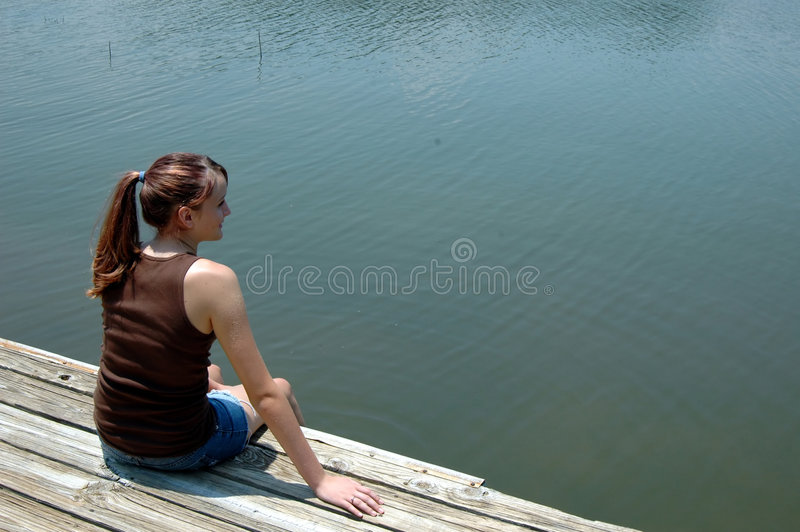 Girl at lake on dock stock photography
