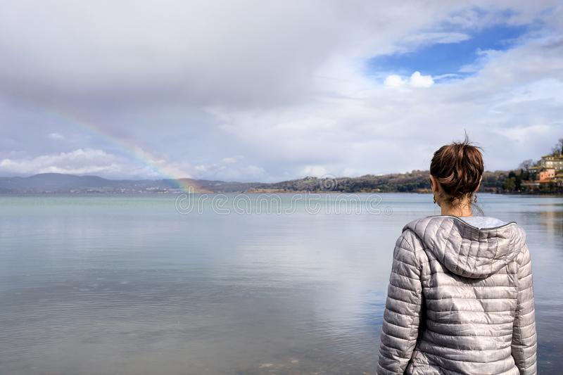 Girl at the lake and rainbow stock photos