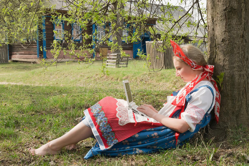 Girl with a laptop. In a rural landscape stock image
