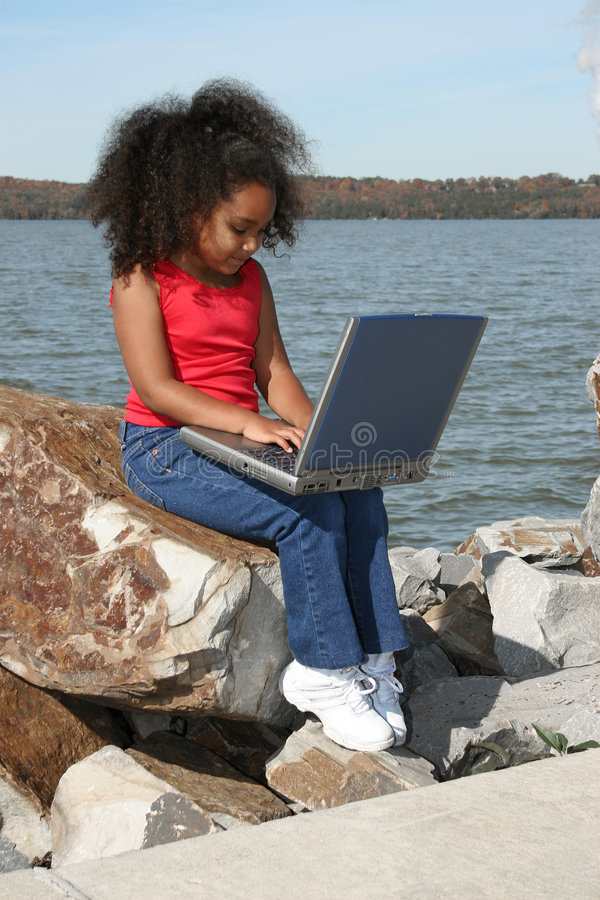 Girl with Laptop. A little African American girl sitting with a laptop on a rock on the banks of a river royalty free stock images
