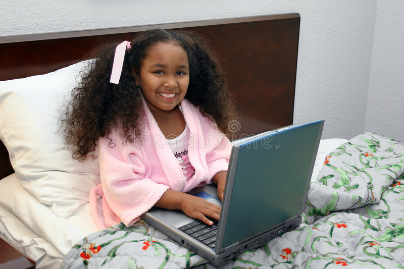 Girl with laptop in bed. African American girl using a laptop while in bed stock photography