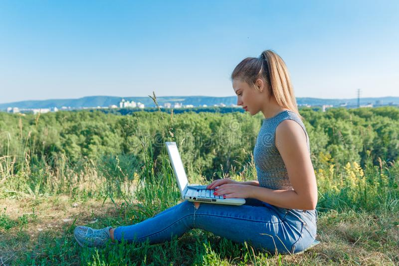 Girl with laptop on the nature on the background of forest and sky. The concept of combining leisure and work. Individual stock images