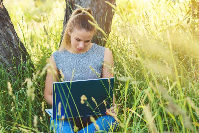 A girl with a laptop in nature among the green grass. royalty free stock images