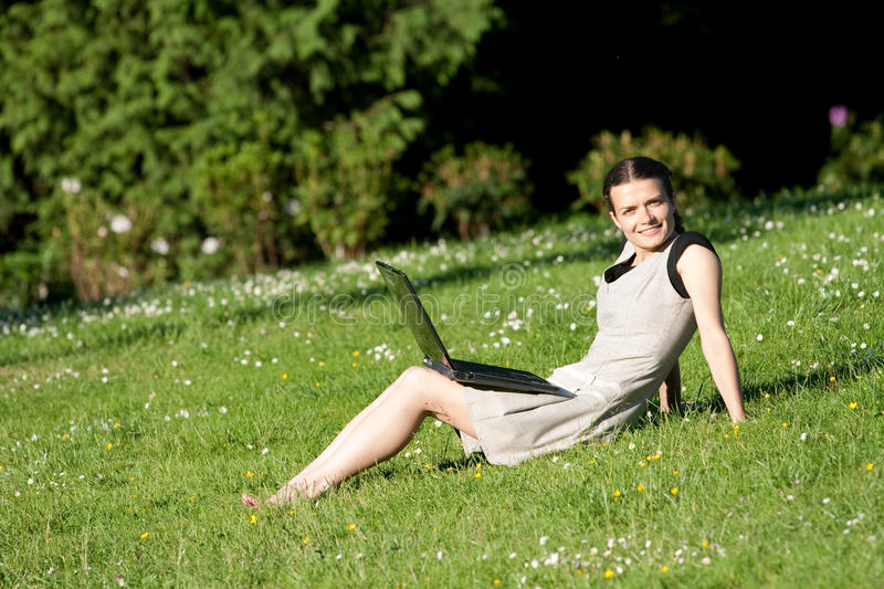 Girl with a laptop in a park royalty free stock photos