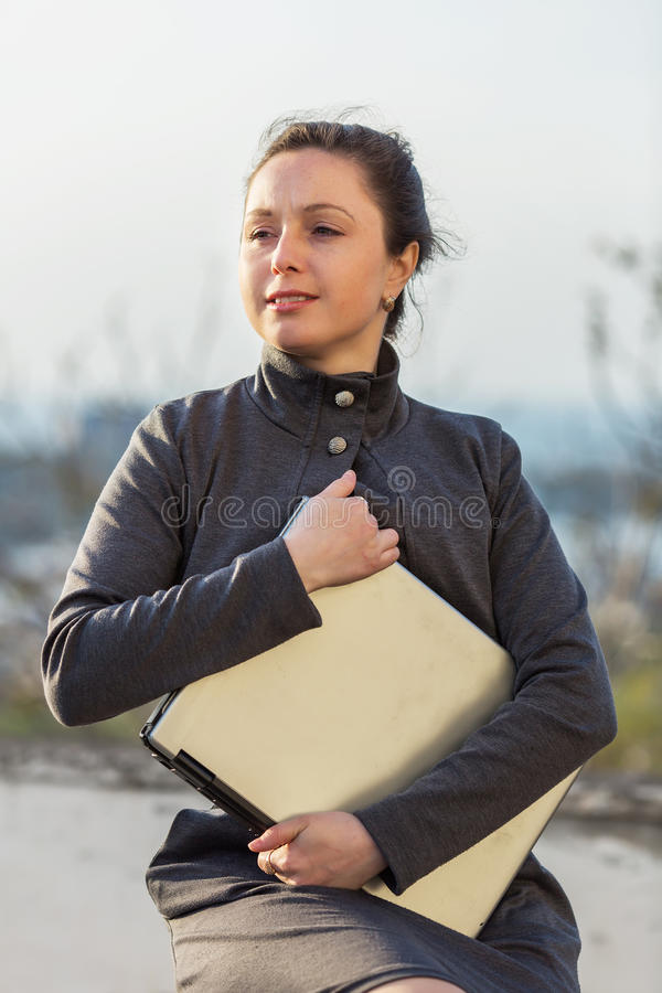 Girl with laptop sitting on open air stock photos
