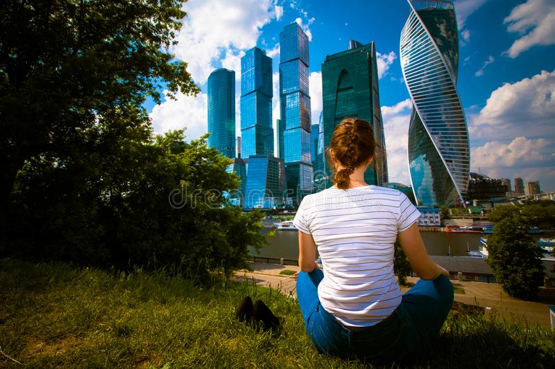 Girl sitting on the grass and relaxing. She is in blue jeans and a white t-shirt. Landscape with skyscrapers stock photo