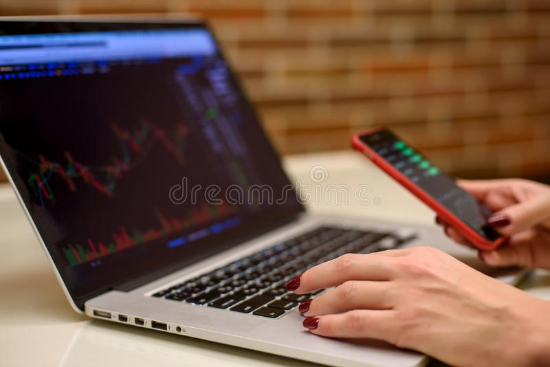 Girl with laptop and smartphone watching bitcoin graphs and stocks. On a laptop screen royalty free stock photography
