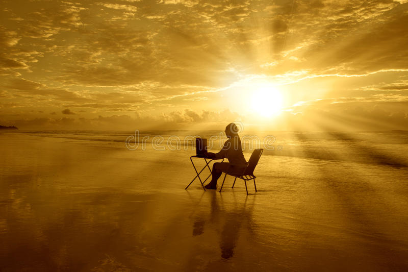 Girl-with-laptop-at-sunset-on-the-beach royalty free stock photo