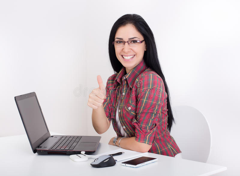 Girl with laptop and thumb up. Beautiful young girl sitting at table with laptop and showing thumb up. Isolated on white background royalty free stock image