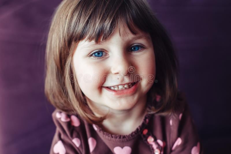 Girl with large blue eyes looking in camera stock image