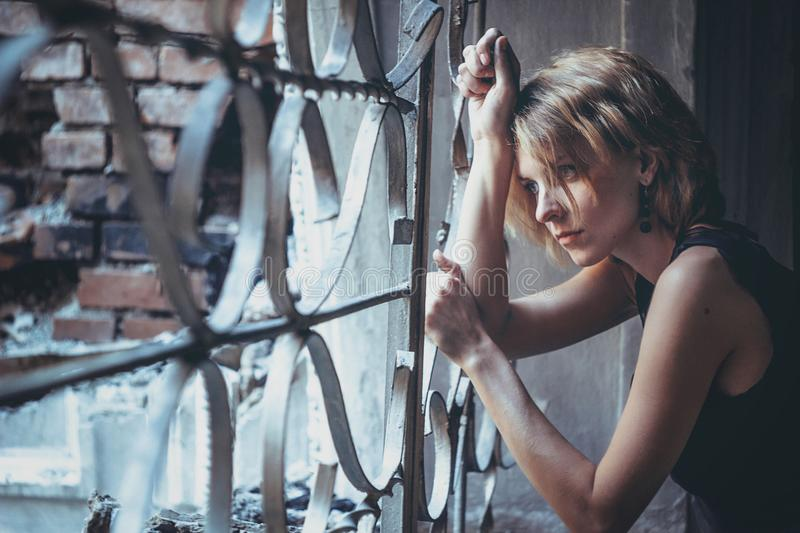 The girl at lattice Windows. The girl in the old ruined house in the ward stock photos