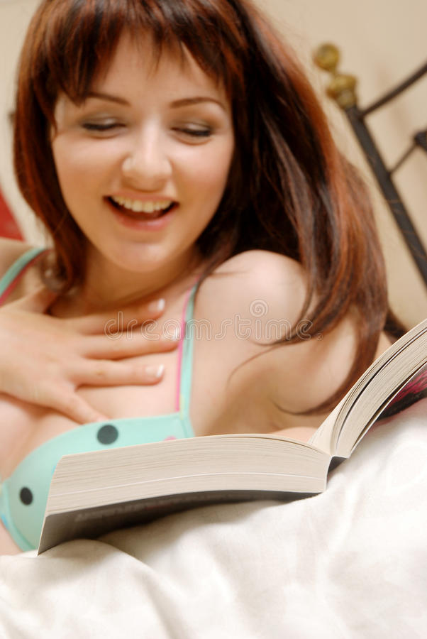 Girl laughing at her book stock image