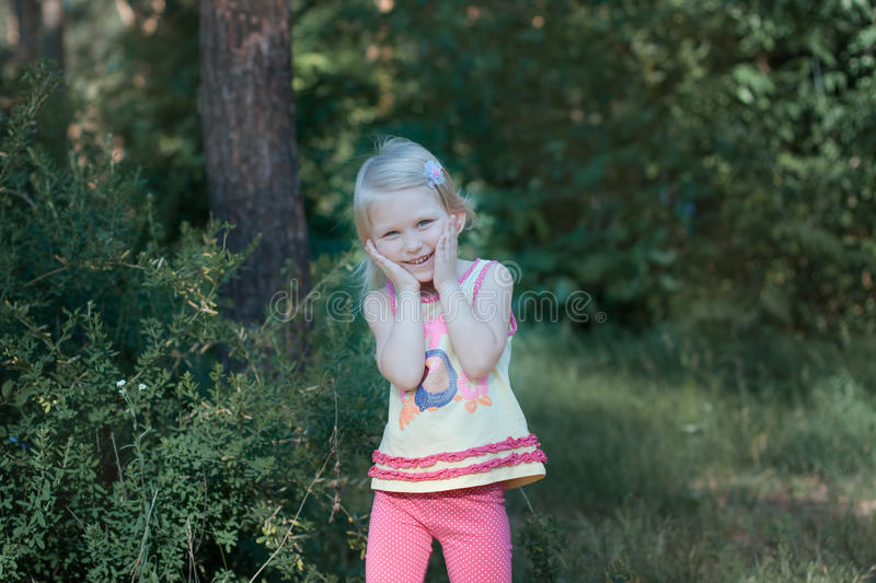Girl laughing his head bowed. Little beautiful blonde girl standing in the forest. She girl put her face in her hands and bowed her head, she laughs stock image