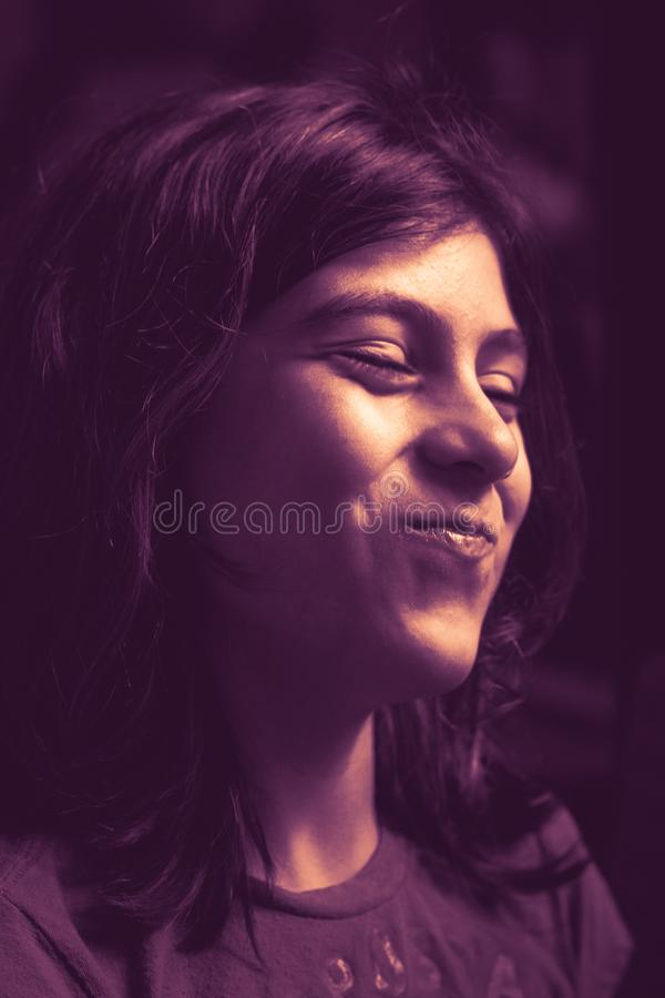 Girl laughing with his mouth full and closed eyes royalty free stock photos