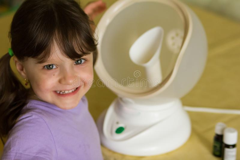 The girl laughs next to a round white steam inhaler is treated for flu and cold. On the table are bottles of essential oils and. Medicines. horizontal photo royalty free stock images