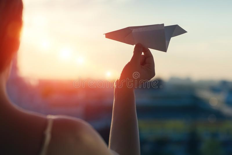 A girl is launching a paper airplane from a window at sunset. Support of the Telegram application and freedom internet. A popular messenger Telegram is banned stock photography