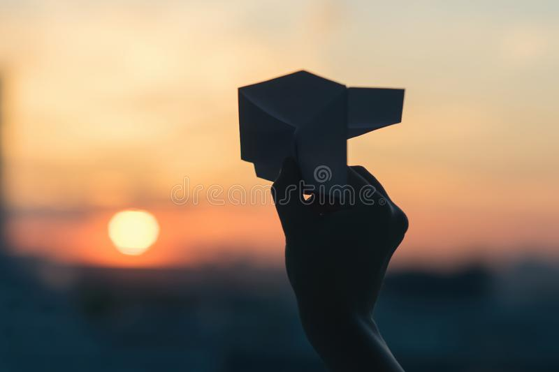 A girl is launching a paper airplane from a window at sunset. Support of the Telegram application and freedom internet. A popular messenger Telegram is banned stock photo