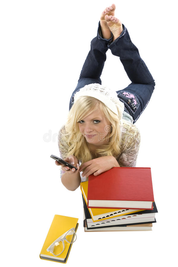 Girl laying behind books texting. royalty free stock photos