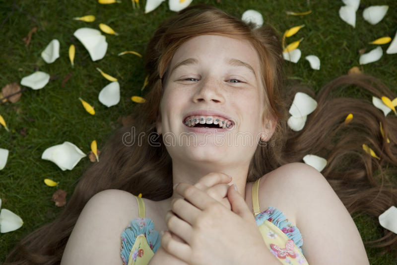 Girl Laying on Grass and Petals royalty free stock photography